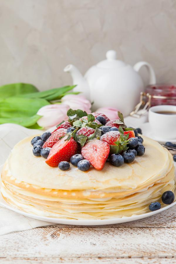 Crepes cake with cottage cheese and strawberry, selective focus. Homemade crepes cake with strawberry on rustic background. Cooking fresh homemade breakfast royalty free stock image