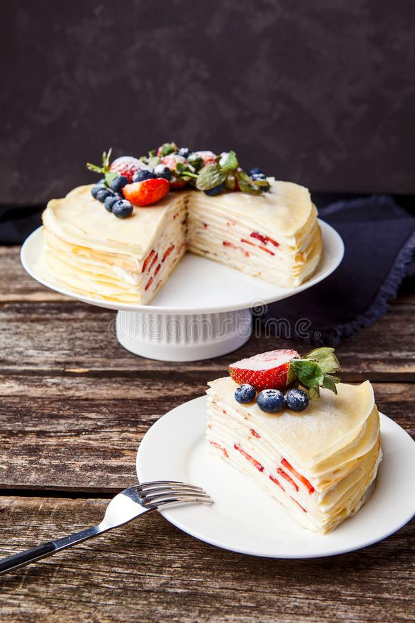Crepes cake with cottage cheese and strawberry, selective focus. Homemade crepes cake with strawberry on rustic background. Cooking fresh homemade breakfast stock photography