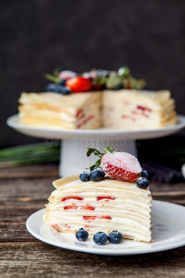 Crepes cake with cottage cheese and strawberry, selective focus. Homemade crepes cake with strawberry on rustic background. Cooking fresh homemade breakfast stock image