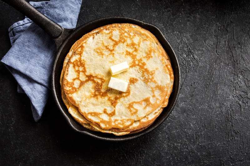 Crepes in cast iron pan. Homemade crepes with butter in cast iron pan over rustic black background with copy space - cooking fresh homemade breakfast crepes stock image