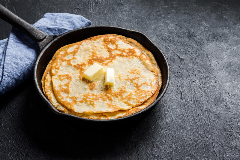 Crepes in cast iron pan. Homemade crepes with butter in cast iron pan over rustic black background with copy space - cooking fresh homemade breakfast crepes stock photography