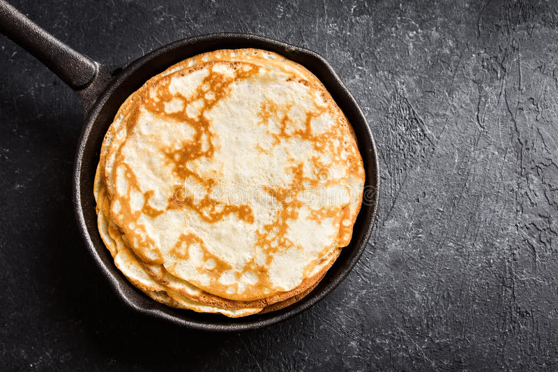 Crepes in cast iron pan. Homemade crepes in cast iron pan over rustic black background with copy space - cooking fresh homemade breakfast crepes pancakes food royalty free stock photo