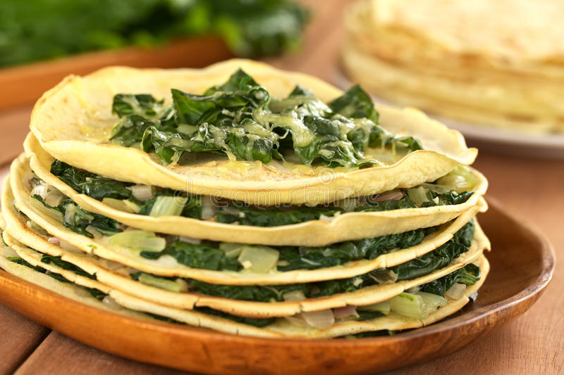 Crepes with Chard. Fresh homemade savory crepes layered with chard (mangold) and onion with cheese on top served on wooden plate (Selective Focus, Focus on the stock photography