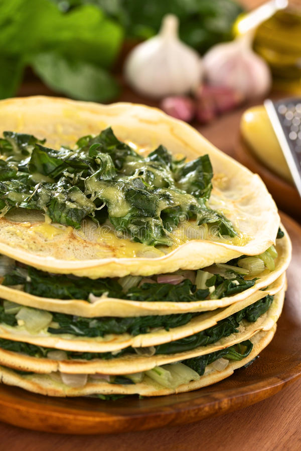 Crepes with Chard. Fresh homemade savory crepes layered with chard (mangold) and onion with cheese on top served on wooden plate with ingredients in the back ( stock photography