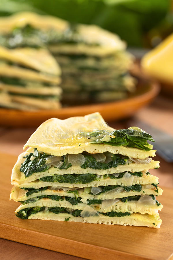 Crepes with Chard. A piece of fresh homemade savory crepes layered with chard (mangold) and onion with cheese on top on wooden board (Selective Focus, Focus on stock photography