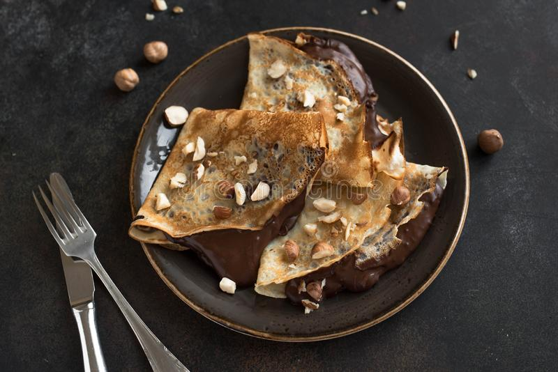 Crepes with chocolate. And hazelnuts. Homemade thin crepes for breakfast or dessert royalty free stock photos
