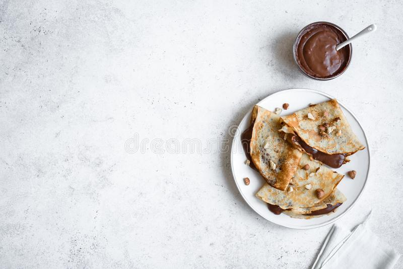 Crepes with chocolate and nuts. Crepes with chocolate spread and hazelnuts. Homemade thin crepes for breakfast or dessert on white, copy space royalty free stock photography