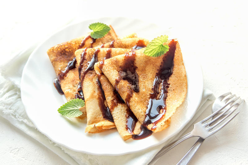 Crepes. With chocolate sauce and mint on white plate over white background, copy space. Delicious homemade  for breakfast stock photos