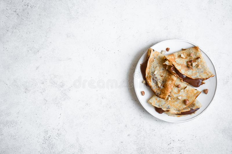 Crepes with chocolate. Spread and hazelnuts. Homemade thin crepes for breakfast or dessert on white, copy space royalty free stock images