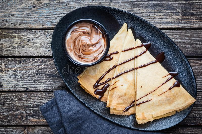 Crepes with chocolate spread. Homemade thin crepes for breakfast or dessert on wooden background, top view stock image