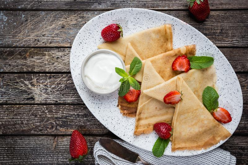 Crepes with chocolate spread. Crepes with strawberry and cream sauce. Homemade thin crepes for breakfast or dessert on wooden background, top view royalty free stock image