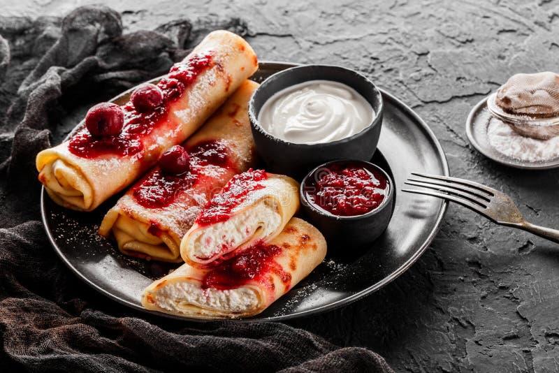 Crepes com açúcar do requeijão, do doce do fruto, das cerejas, do creme de leite e de crosta de gelo na placa preta sobre o fundo imagens de stock