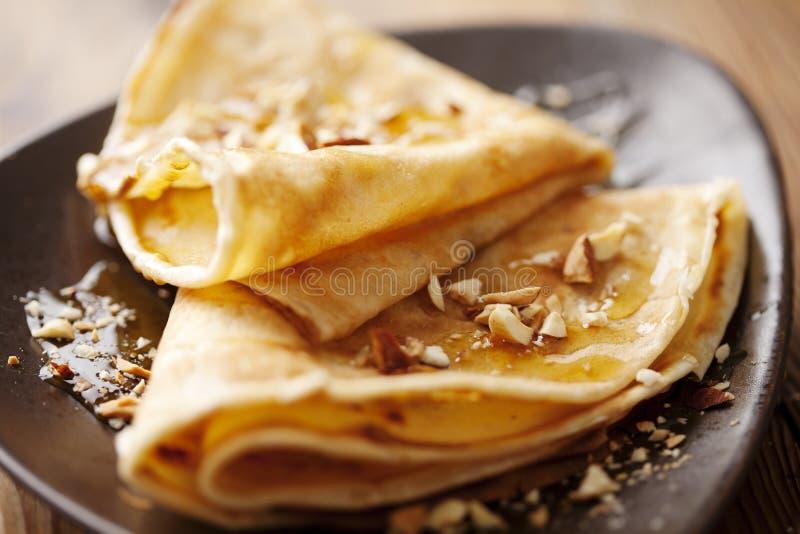 Crepes con la miel o jarabe y tuercas asadas foto de archivo