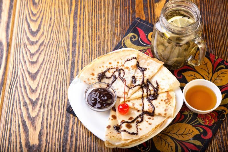 Crepes con la salsa y el té de chocolate con la miel fotografía de archivo