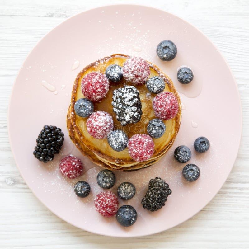 Crepes con las bayas, la miel y el azúcar en una placa rosada en una tabla de madera blanca, visión de arriba Endecha plana, visi imagen de archivo libre de regalías