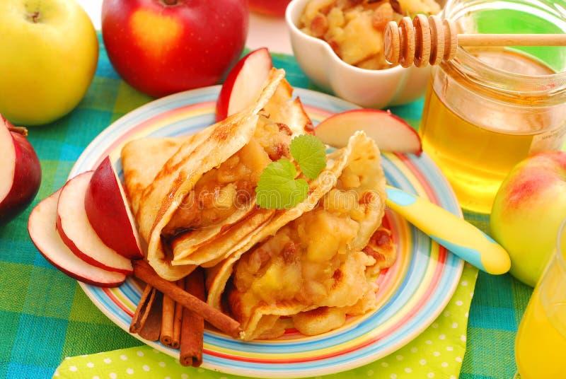 Crepes con las manzanas, las pasas y la miel guisadas fotografía de archivo libre de regalías