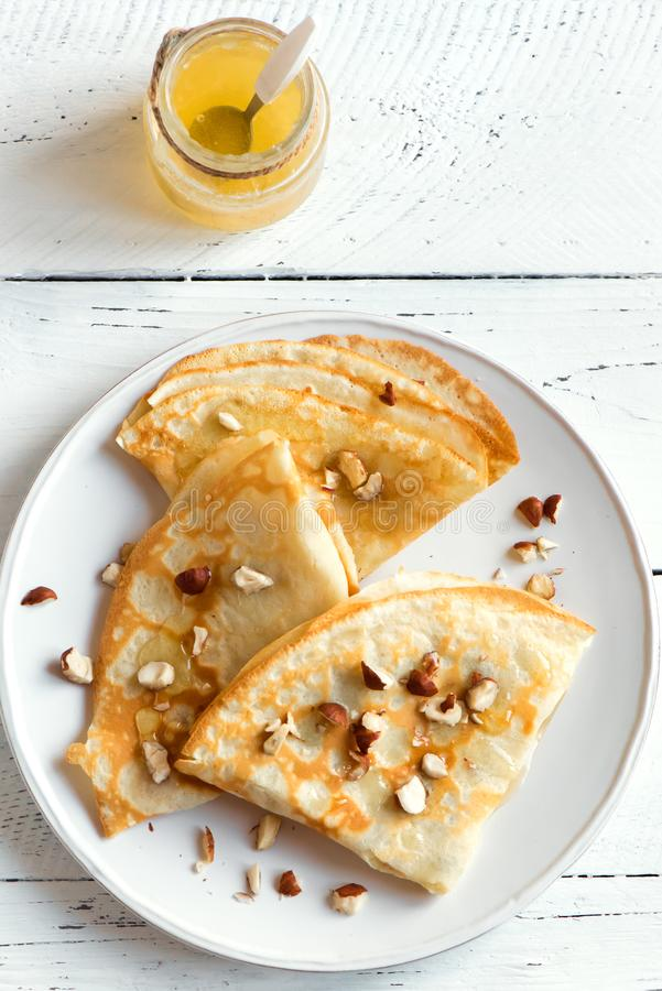 Crepes. Suzette with honey and nuts on white plate over white background, copy space. Delicious homemade  for breakfast royalty free stock photos