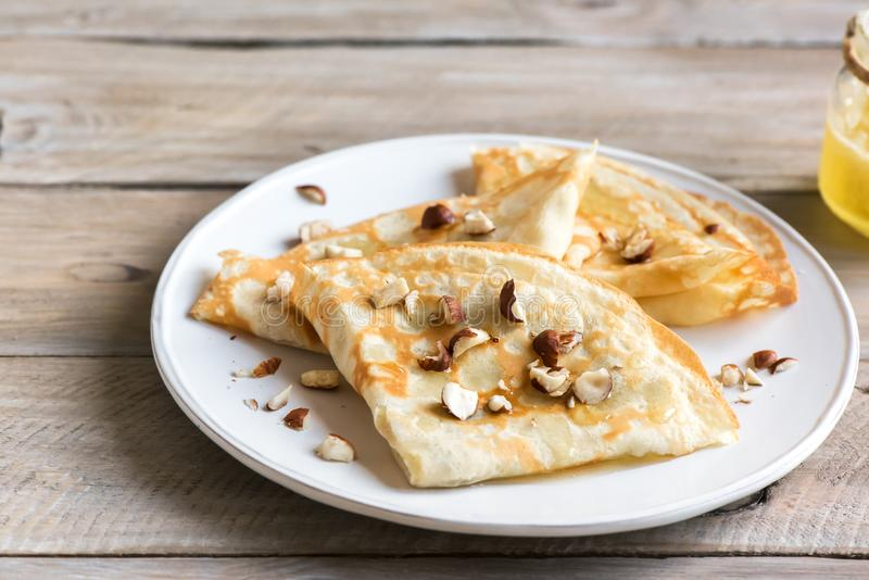 Crepes. Suzette with honey and nuts on white plate over wooden background, copy space. Delicious homemade  for breakfast stock photo