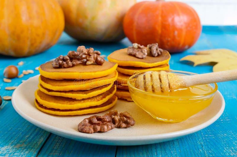 Crepes de oro fragantes de la calabaza con la miel y las nueces en un fondo de madera azul fotos de archivo libres de regalías