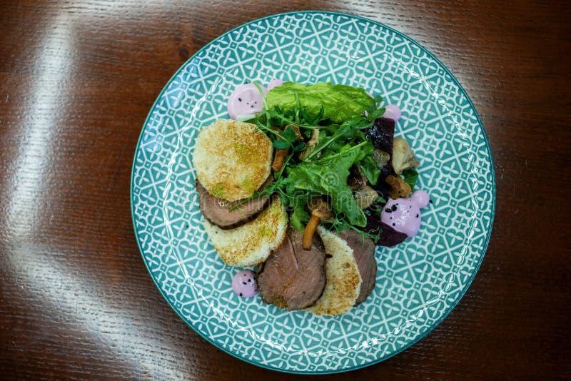 Crepes de patata caliente con los pedazos sabrosos de carne curada con las setas con las hierbas frescas en una tabla de madera d imagen de archivo