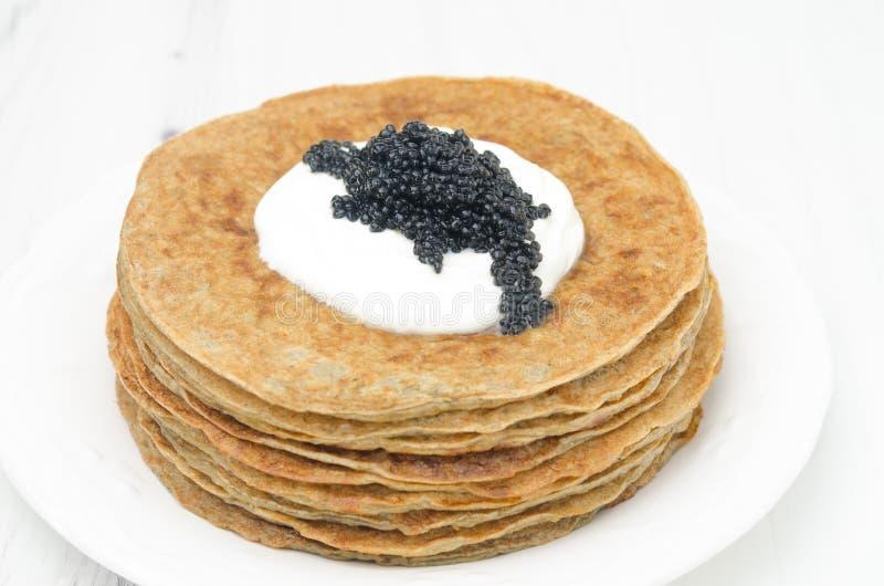 Crepes de patata con crema agria y el caviar en el fondo blanco imágenes de archivo libres de regalías