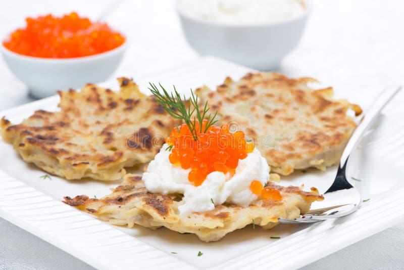 Crepes de patata con el caviar y la crema agria rojos imagen de archivo libre de regalías