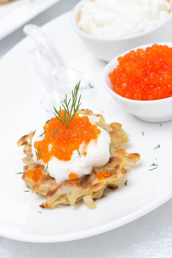 Crepes de patata con el caviar y la crema agria rojos en la placa imagen de archivo