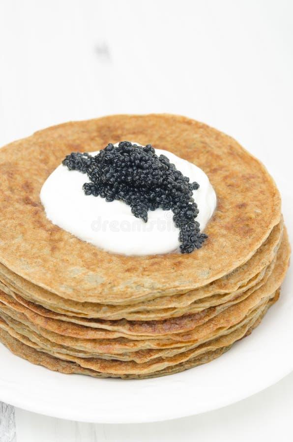 Crepes de patata con el foco selectivo de la crema agria y del caviar foto de archivo