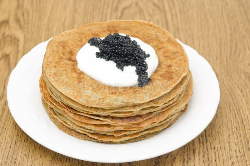 Crepes de patata con la crema agria, foco selectivo del caviar fotos de archivo