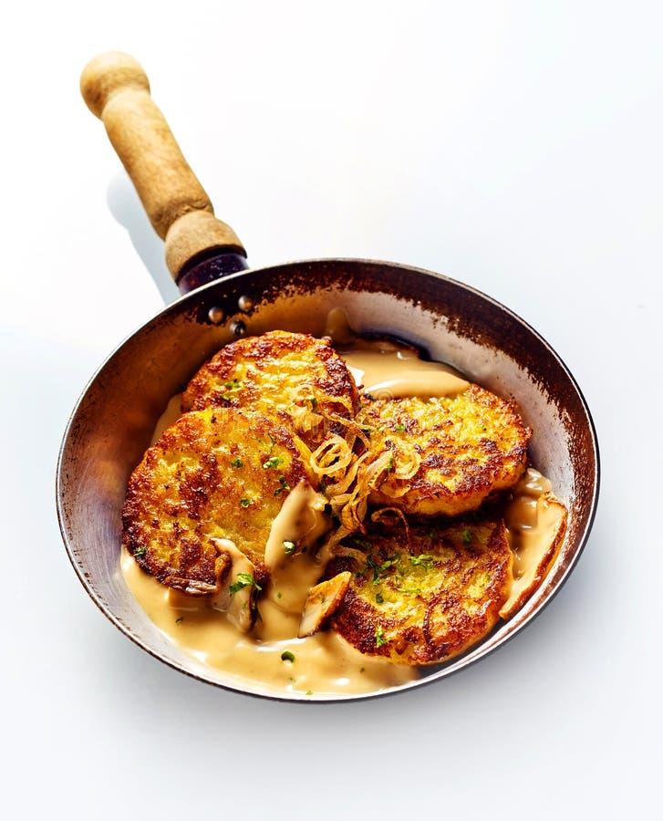 Crepes de patata de oro en cacerola con la salsa cremosa fotos de archivo