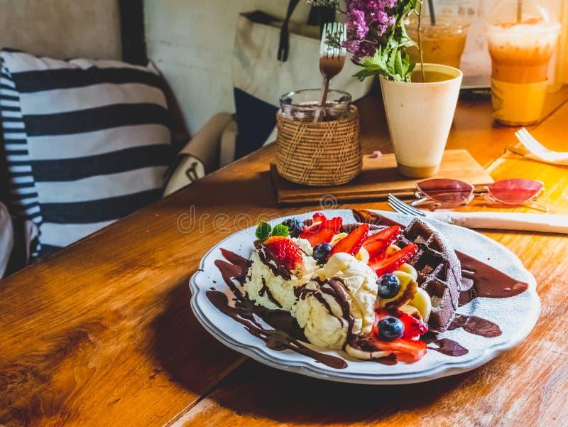 Crepes del chocolate con el plátano, fresa, arándano, nata montada y helado de vainilla, azúcar de formación de hielo, brownie y  imágenes de archivo libres de regalías