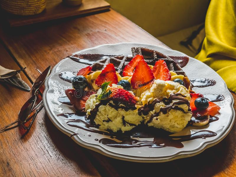 Crepes del chocolate con el plátano, fresa, arándano, nata montada y helado de vainilla, azúcar de formación de hielo, brownie y  imagenes de archivo