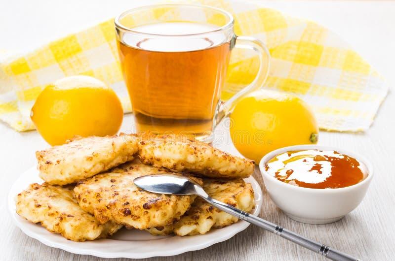 Crepes del requesón, atasco del albaricoque, limones y té en la tabla fotos de archivo