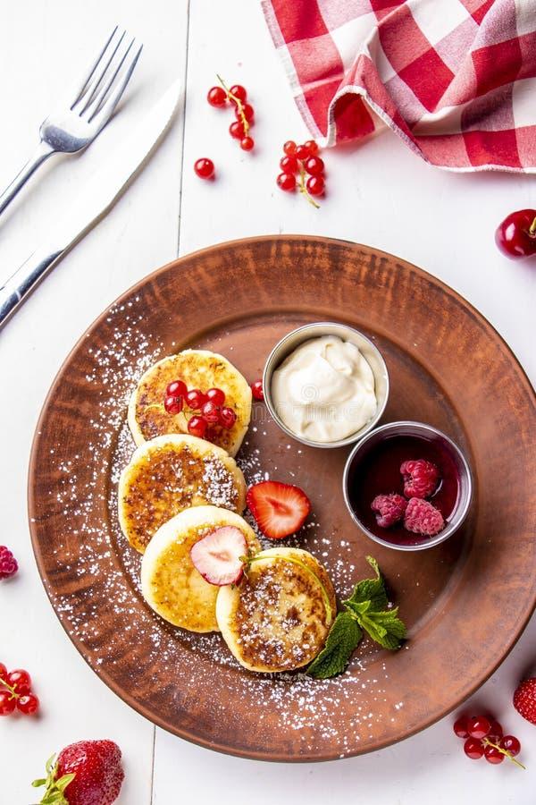 Crepes del requesón, syrniki ucraniano tradicional hecho en casa del plato con la salsa de la baya y crema agria en una placa mar imagenes de archivo