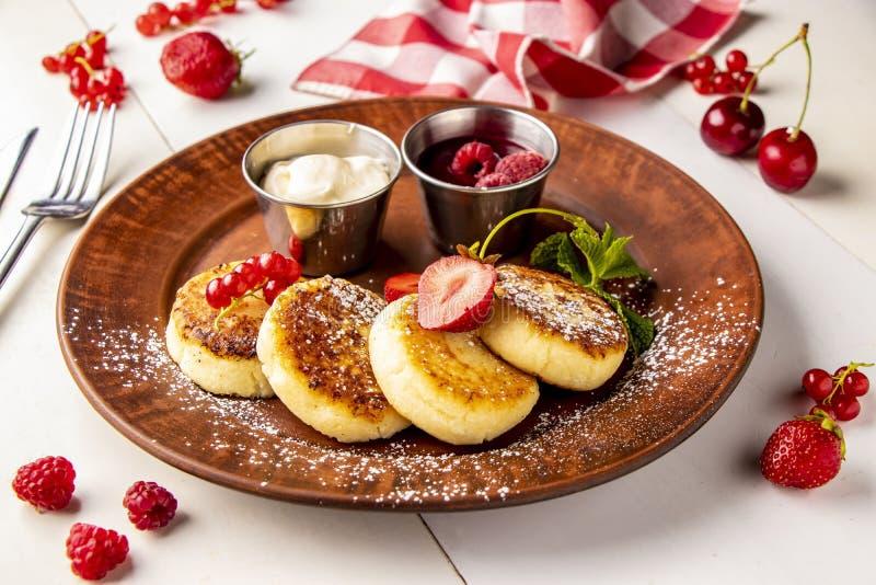 Crepes del requesón, syrniki ucraniano tradicional hecho en casa del plato con la salsa de la baya y crema agria en una placa mar imágenes de archivo libres de regalías
