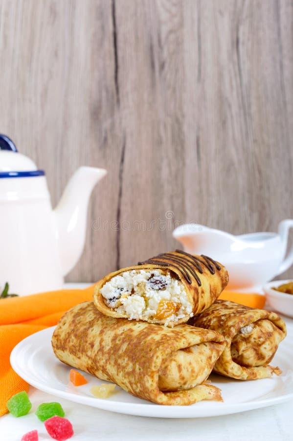 Crepes delicadas deliciosas con reques?n y pasas en un fondo de madera blanco Opinión vertical del desayuno sano fotos de archivo libres de regalías