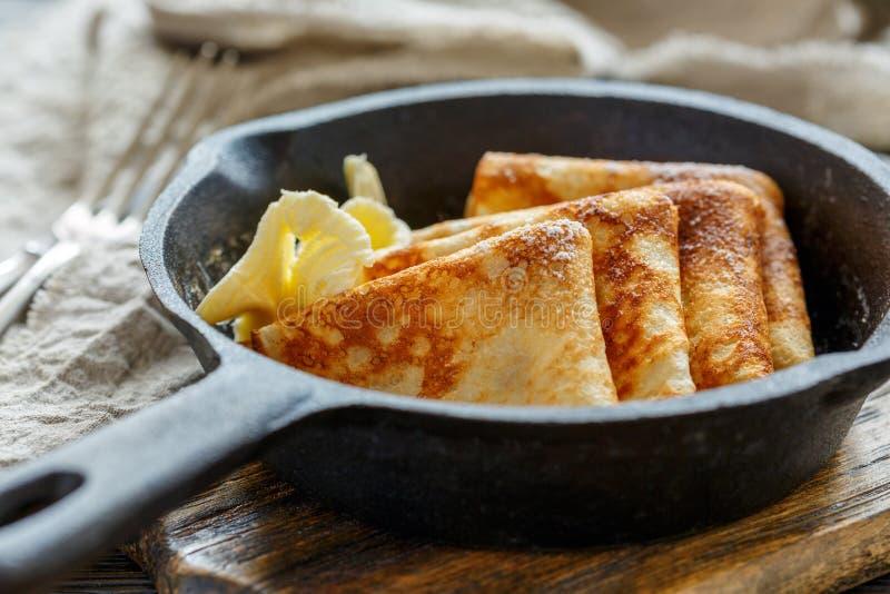 Crepes deliciosos com manteiga em uma bandeja do ferro fundido foto de stock