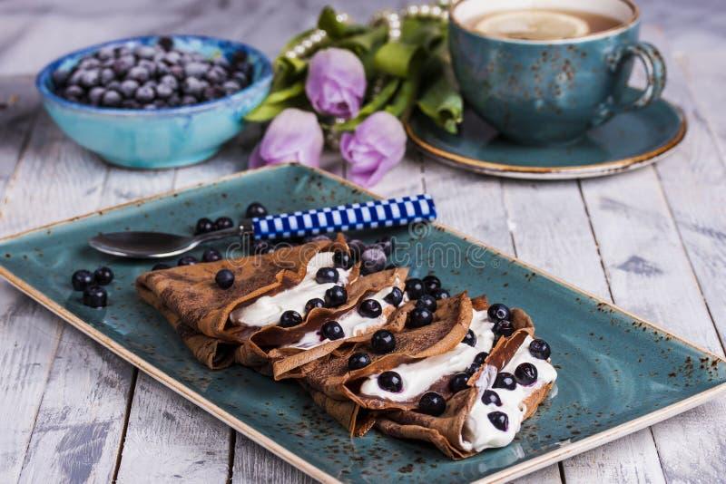 Crepes do chocolate com queijo creme e mirtilos imagens de stock royalty free