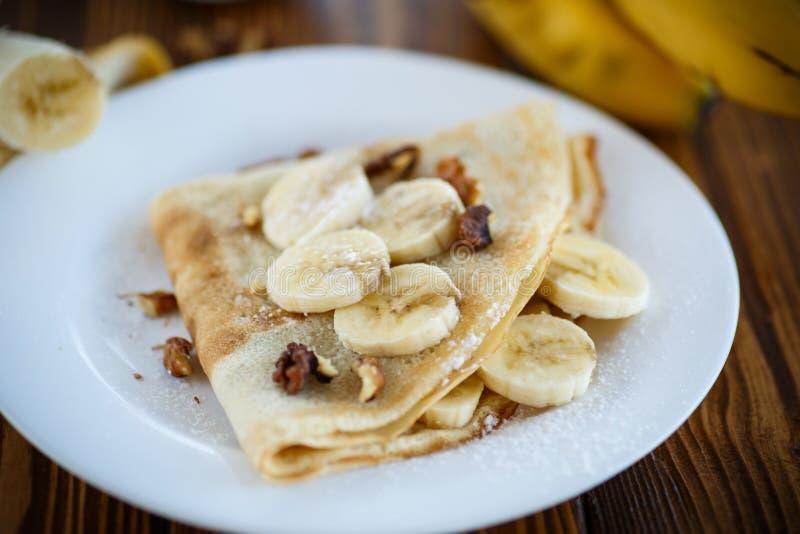 Crepes dulces con los plátanos y las nueces imagenes de archivo