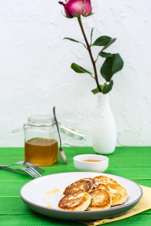 Crepes dulces preparadas del requesón con la miel en una placa imágenes de archivo libres de regalías