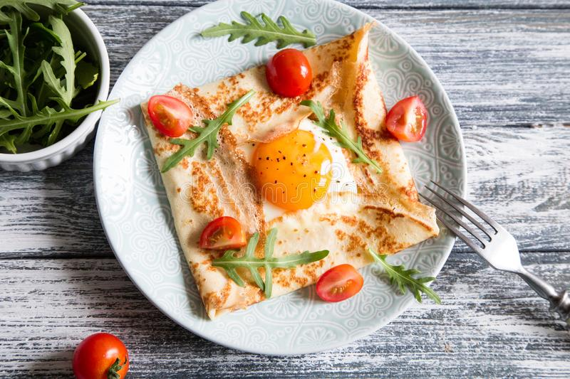 Crepes with eggs, cheese, arugula leaves and tomatoes. Galette complete. Traditional dish galette sarrasin stock photos