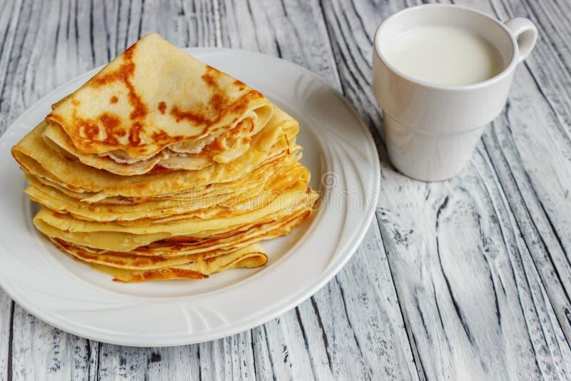 Crepes en una placa blanca con la miel y una taza de leche Desayuno sabroso foto de archivo libre de regalías