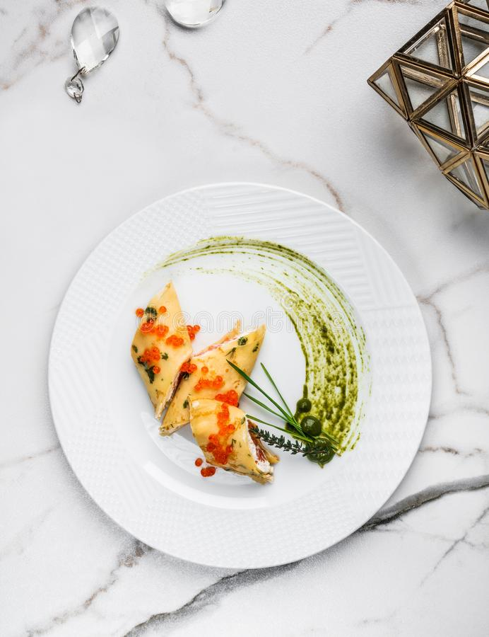 Crepes with filet salmon and cheese, red fish caviar and green sauce on white plate over marble background. Pancake week or Shrovetide. Healthy breakfast. Top stock image