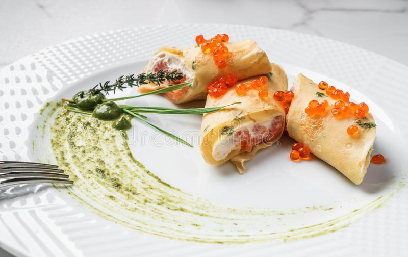 Crepes with filet salmon and cheese, red fish caviar and green sauce on white plate over marble background royalty free stock image