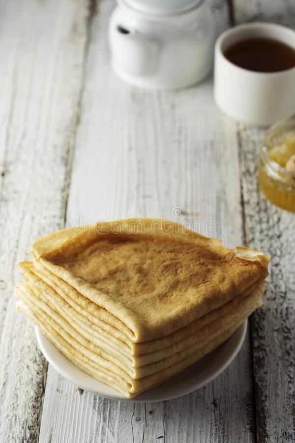 Crepes Crepes finas Bliny ruso Desayuno sabroso sano - crepes, una taza de té y miel Copie el espacio imagen de archivo
