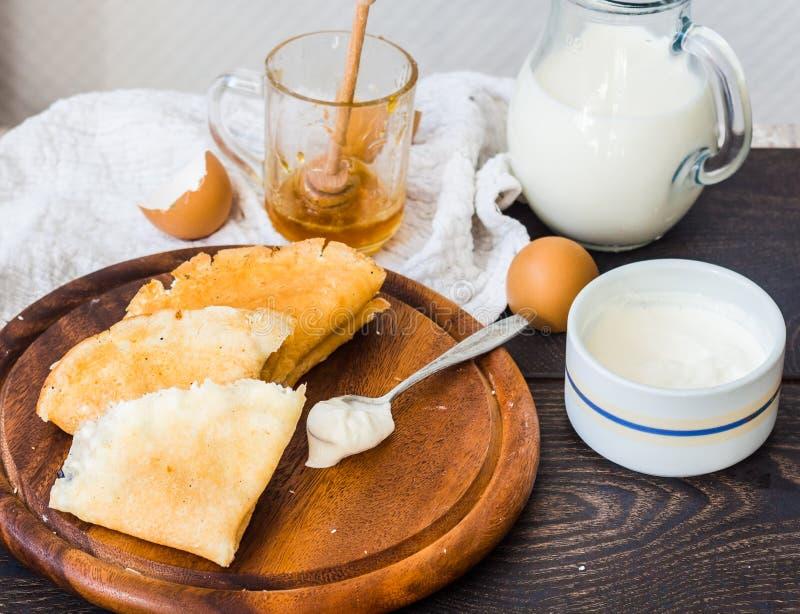 Crepes finas con requesón, las pasas, la miel y la crema agria fotografía de archivo