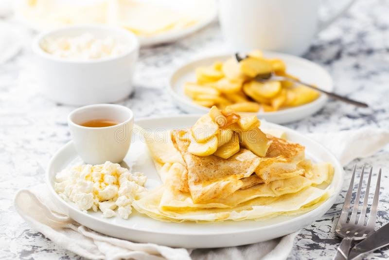 Crepes finas tradicionales con la manzana, el requesón y la miel en una placa blanca imagenes de archivo