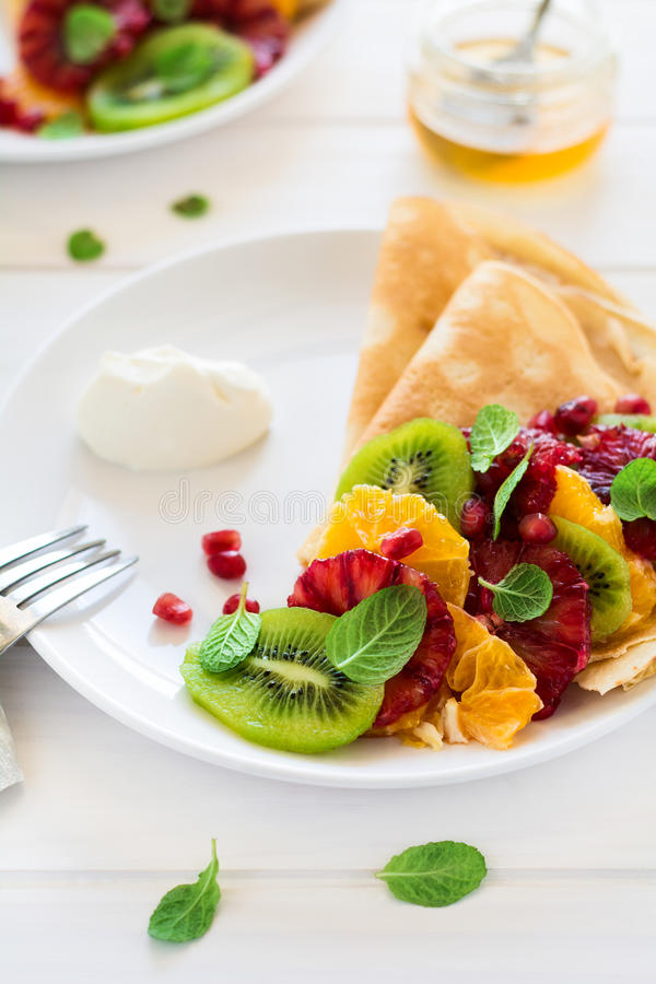 Crepes finos com quivi fresco, laranja, as folhas sicilianos da laranja, do mel, do creme e de hortelã imagens de stock royalty free