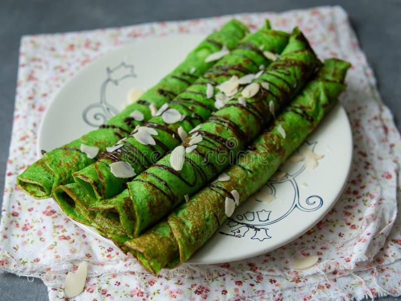 Crepes finos da hortelã da cor verde, torcidos nos tubos, com as pétalas do molho de chocolate e da amêndoa em uma placa branca n foto de stock