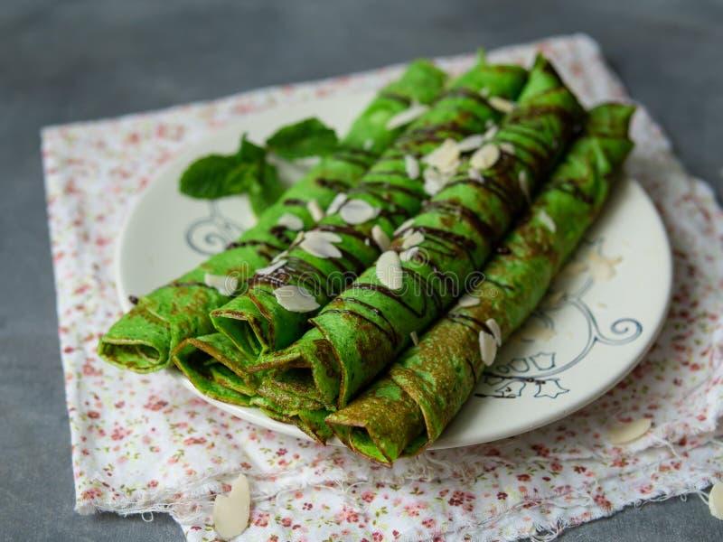 Crepes finos da hortelã da cor verde, torcidos nos tubos, com as pétalas do molho de chocolate e da amêndoa em uma placa branca n fotos de stock
